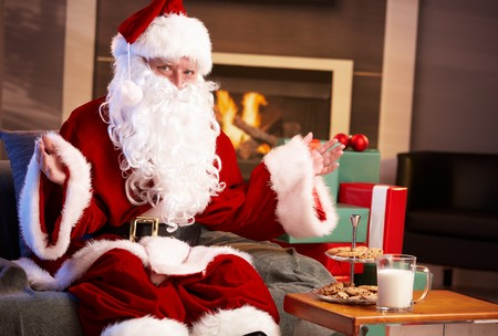 Satisfied Santa Claus sitting at fireplace happy to get milk and chocolate chip cookies, looking at camera. photo