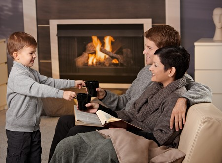 fireplace family: Happy family sitting on couch at home in front of fireplace, drinking tea, smiling. Stock Photo