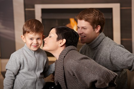 Happy family sitting on couch at home in front of fireplace, looking at camera, smiling. Stock Photo - 7962051