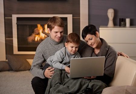 Happy family sitting on couch at home in winter, using laptop computer, smiling. photo