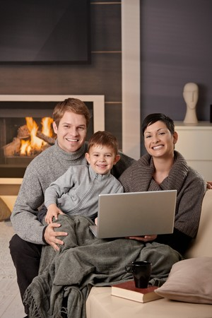 Happy family sitting on couch at home in winter, using laptop computer, looking at camera, smiling. photo
