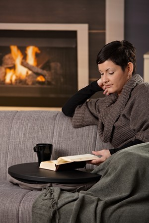 Woman sitting on sofa at home on a cold winter day, reading book. photo