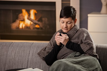 Woman sitting on sofa at home on a cold winter day, drinking hot tea, looking down. photo
