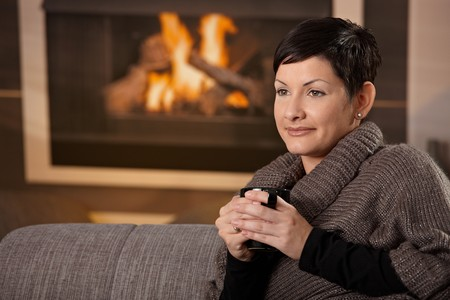 Woman sitting on sofa at home on a cold winter day, drinking hot tea, looking away. photo