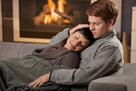 Young couple hugging on sofa in front of fireplace at home, woman sleeping. photo