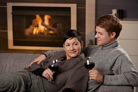 Young romantic couple sitting on sofa in front of fireplace at home, drinking red wine. Stock Photo - 7962057