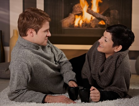 Young couple lying on floor in front of fireplace at home, talking, smiling. photo