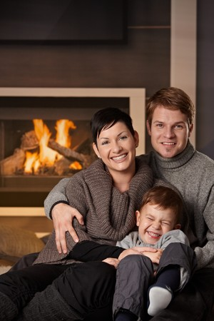 Happy family sitting on couch at home in a cold winter day, looking at camera, laughing. photo