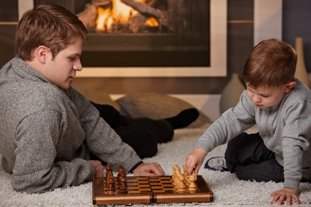 Father and 4 years old kid playing chess at home in a cold winter day. photo