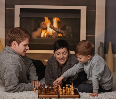 Young family with 4 years old kid playing chess at home in a cold winter day. photo