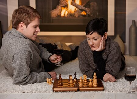 Young couple playing chess at home on a cold winter day. photo