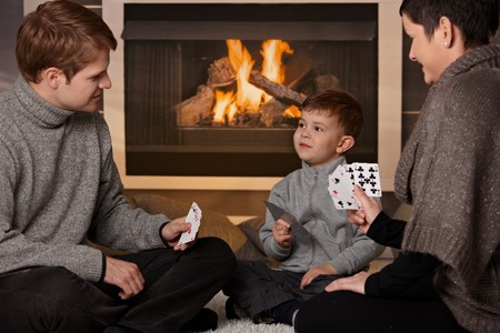Young family with 4 years old kid playing card game at home in a cold winter day. photo