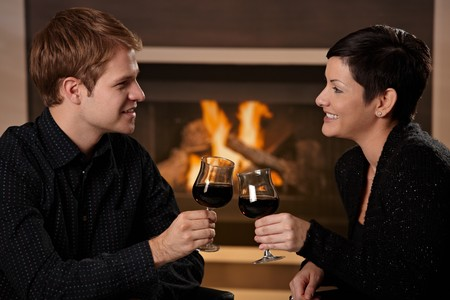 Young romantic couple dating, sitting in front of fireplace at home, drinking red wine. Stock Photo - 7962030