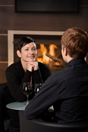 Young romantic couple dating, sitting in front of fireplace at home, drinking red wine. Stock Photo - 7962021