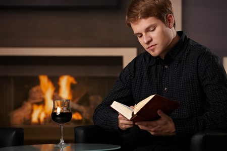 well read: Young man sitting in front of fireplace at home on a cold winter day, reading book. Stock Photo