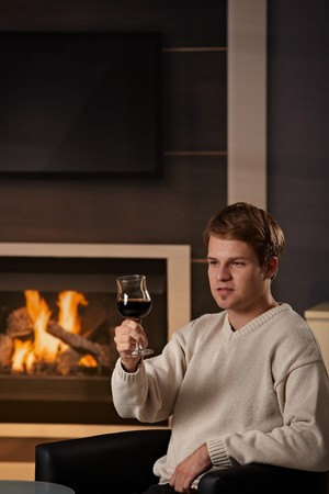 Young man sitting on sofa at home on a cold winter day, drinking red wine. photo