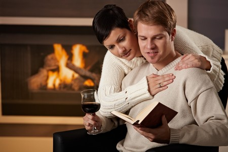 Young couple hugging in front of fireplace at home, reading book. photo
