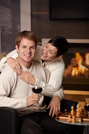 Happy young couple hugging in front of fireplace at home, looking at camera, smiling. Stock Photo - 7962035