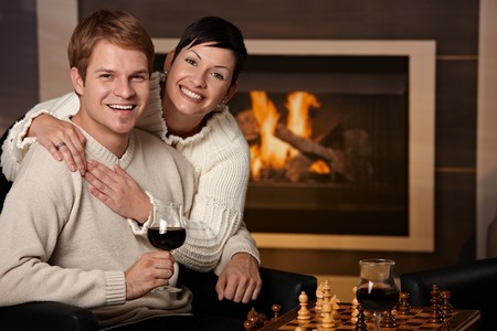 Happy young couple hugging in front of fireplace at home, looking at camera, smiling. Stock Photo - 7962042