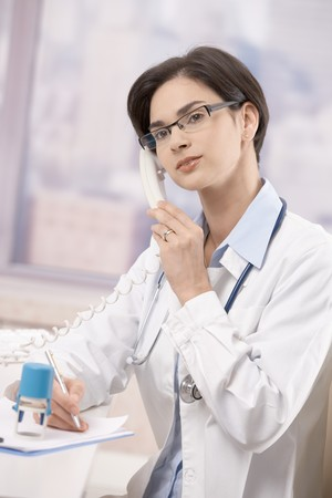 Attractive mid-adult female doctor working at desk in office talking on landline phone. photo