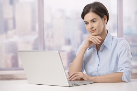 Portrait of mid adult businesswoman sitting at skyscraper office table looking at laptop computer screen. photo