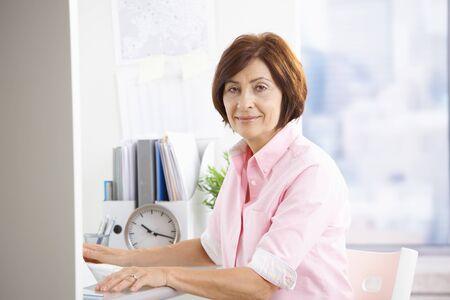 Portrait of mature office worker sitting at desk, smiling at camera. photo