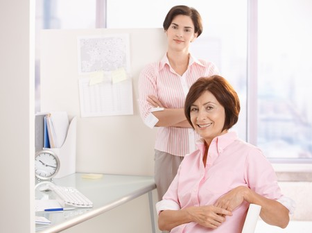co worker: Portrait of two female office workers, smiling at desk, looking at camera.