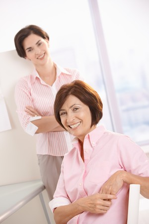 Portrait of female colleagues in office, smiling at camera. photo