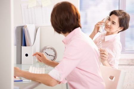 Coworkers sitting together at desk, woman speaking on landline phone, smiling at coworker. photo