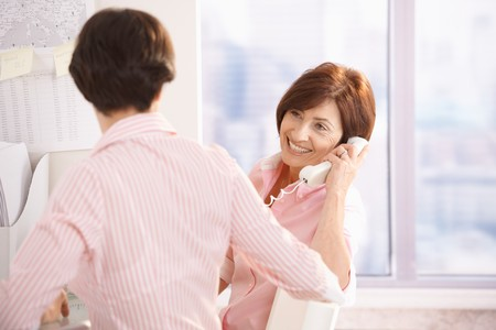 Senior woman talking on landline phone in office, smiling, sitting at desk with young coworker. photo