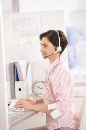 Smiling customer service operator at work, sitting at desk, using computer and headset. photo