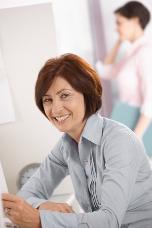 Portrait of smiling mature female office worker sitting at desk, coworker on phone in background. photo