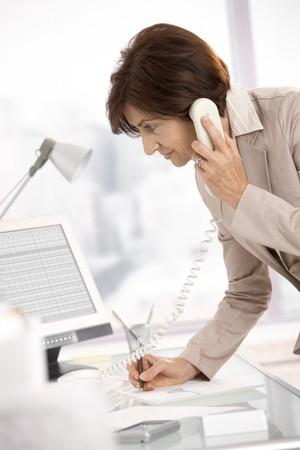 taking note: Businesswoman Senior lavorando in ufficio, in piedi al banco, parlando su telefono fisso, prendendo appunti.