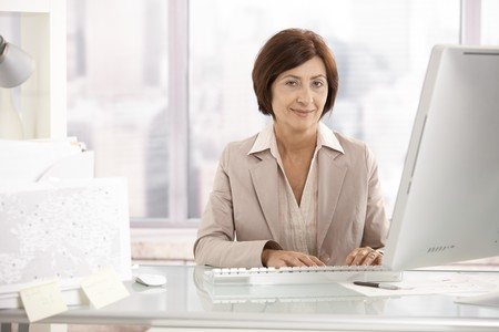 businesswoman: Portrait of senior businesswoman sitting at office desk, smiling at camera.
