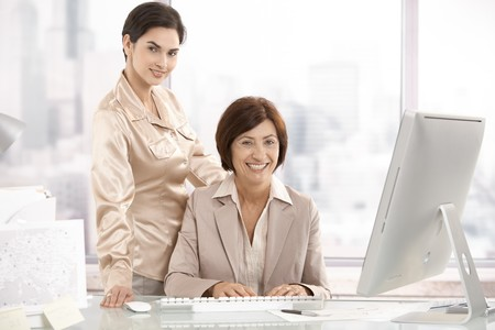 executive assistants: Portrait of senior executive woman with assistant in office, looking at camera, smiling. Stock Photo