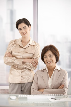 Portrait of businesswomen in office, smiling at camera. photo