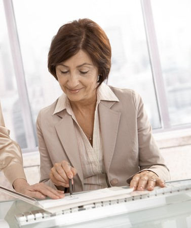 reviewing documents: Smiling senior businesswoman reviewing documents with assistant. Stock Photo