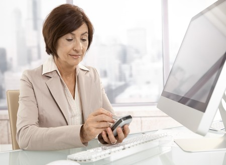 Senior professional woman using pda in office, sitting at desk, smiling. photo