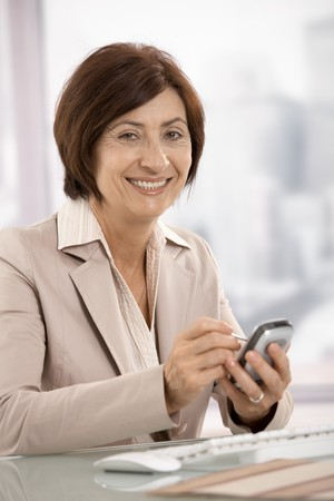 Portrait of senior businesswoman using pda in office, smiling at camera. photo