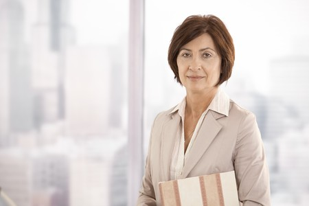 Portrait of senior businesswoman standing in office, looking at camera. photo