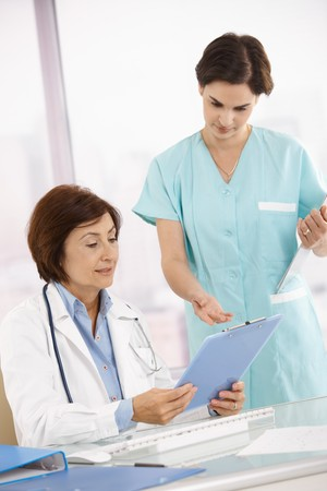 Senior doctor and assistant discussing work in office, holding clipboard. photo