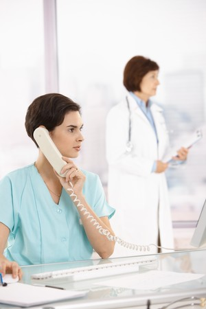 Assistant taking phone call at office desk, medical doctor in background. Stock Photo - 7961990