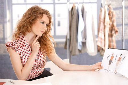 fashion clothing: Young attractive fashion designer working in office at desk thinking. Stock Photo
