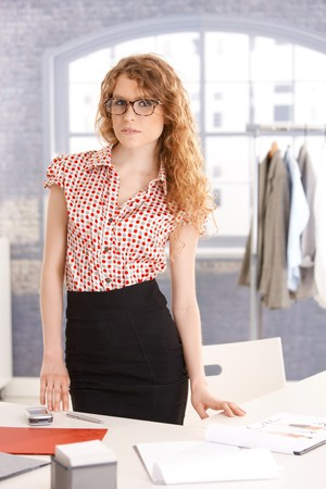 wear: Young attractive female fashion designer working in office at desk.