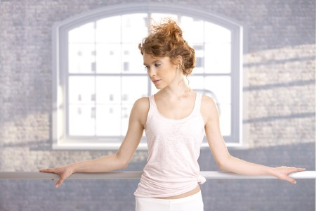 Pretty dancer standing by bar in dance studio front of window. photo
