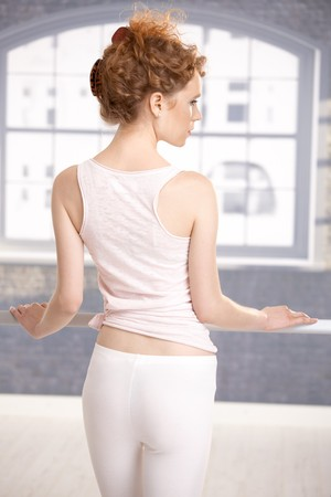 Young girl standing by bar in dance studio front of window showing her back. photo