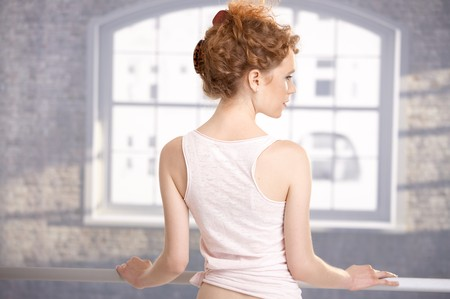ballet bar: Young girl standing by bar in dance studio front of window showing her back.