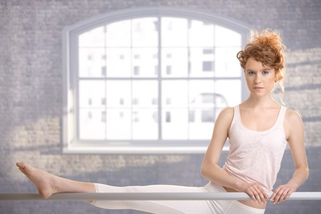 Attractive ballerina girl practicing by bar in dance studio front of window. photo