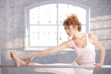 offish: Attractive ballerina girl practicing by bar in dance studio front of window.