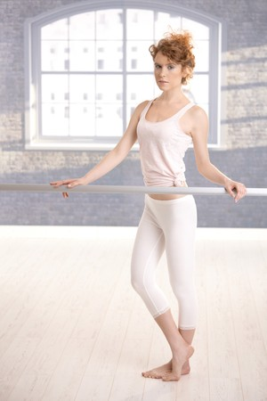 ballet bar: Pretty dancer standing by bar in dance studio front of window. Stock Photo
